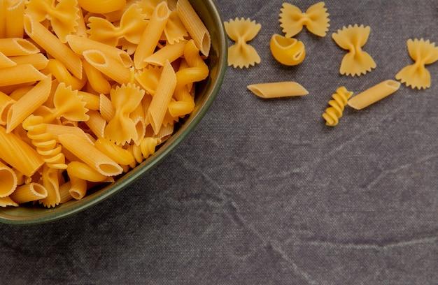 Zijaanzicht van verschillende soorten macaroni op grijze doek