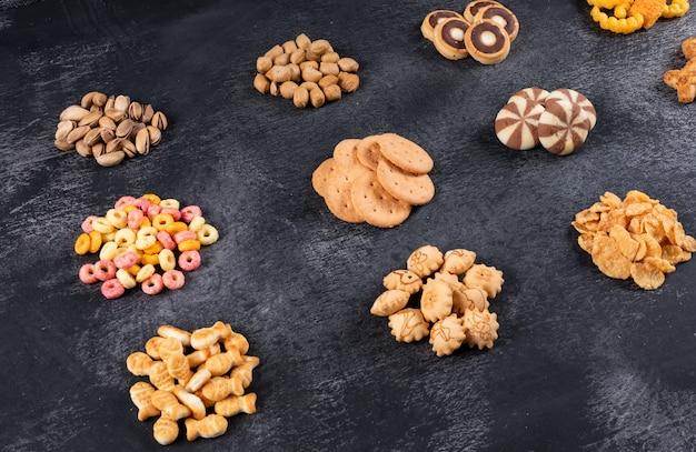 Zijaanzicht van verschillende soorten snacks zoals noten, crackers en coockies op donkere horizontaal