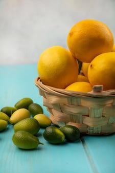 Zijaanzicht van verse citroenen op een emmer met kinkans geïsoleerd op een blauwe houten muur