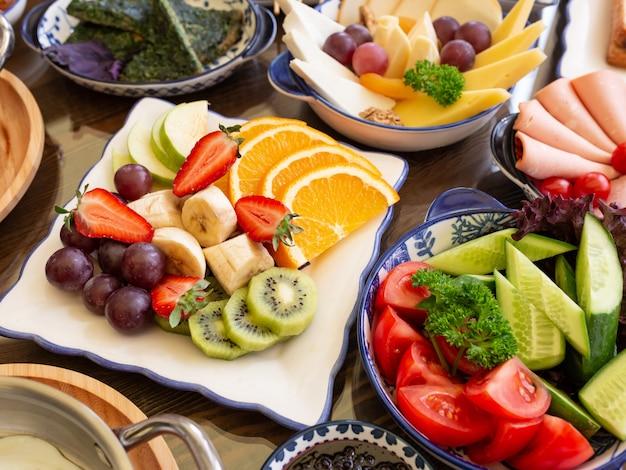 Zijaanzicht van verse groenten en fruit op platen