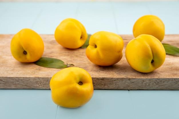 Zijaanzicht van verse heerlijke gele perziken op een houten keukenbord op een blauwe achtergrond
