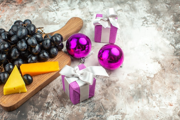 Zijaanzicht van verse heerlijke zwarte druiventros en kaas op houten snijplank