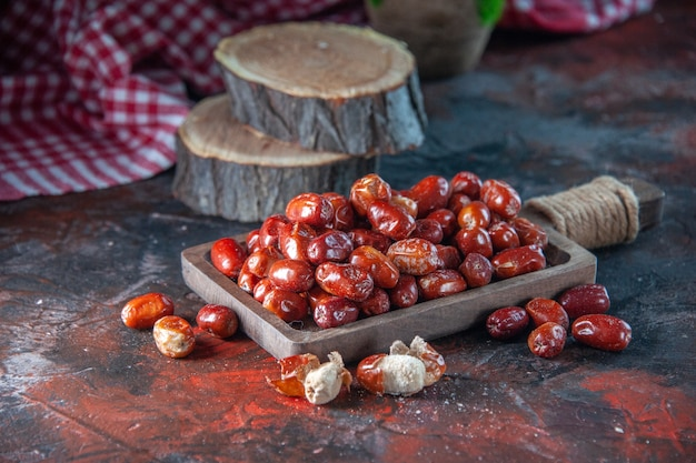 Zijaanzicht van verse rauwe zilverbessenvruchten aan de binnen- en buitenkant van een houten dienblad, bloempot, rode gestripte handdoek op de achtergrond van mixkleuren