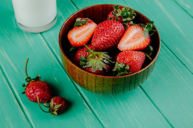 Zijaanzicht van verse rijpe aardbeien in een houten kom met een glas melk op groen hout