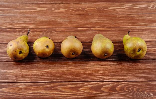 Zijaanzicht van verse rijpe peren in een lijn op een houten achtergrond met kopie ruimte