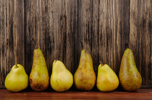 Zijaanzicht van verse rijpe peren in een lijn op een houten achtergrond