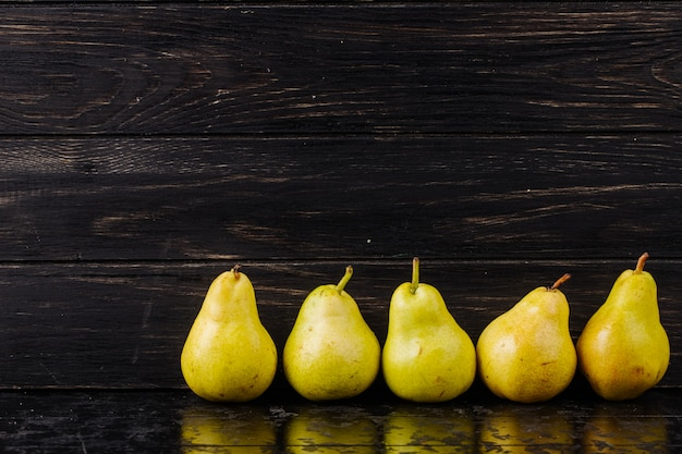 Zijaanzicht van verse rijpe peren in een lijn op zwarte houten achtergrond met kopie ruimte