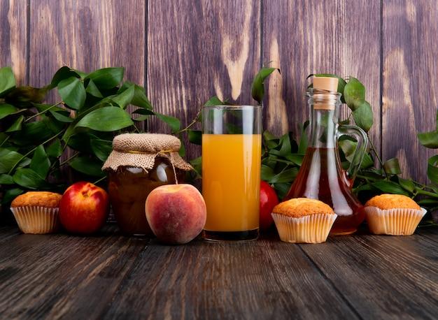 Zijaanzicht van verse rijpe perziken met muffins perzikjam in een glazen pot en perziksap in een glas op rustieke houten tafel