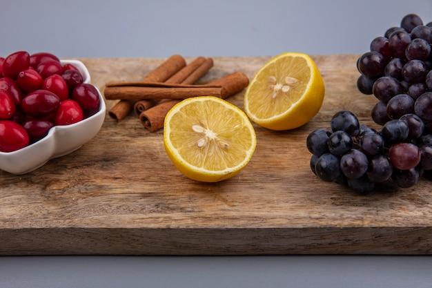 Zijaanzicht van verse rode cornel bessen op een kom met citroen-kaneelstokjes en druiven op een houten keukenbord op een grijze achtergrond