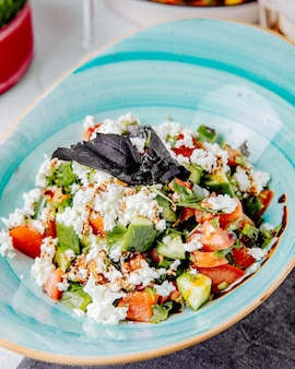 Zijaanzicht van verse salade met de kaas van tomatenkomkommers en basilicum 4