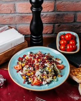 Zijaanzicht van verse salade met de witte kaas van kooltomaten en granaatappelzaden op een plaat