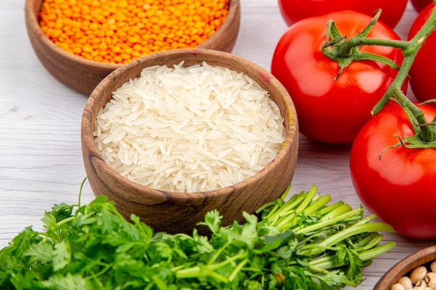 Zijaanzicht van verse tomaten met stengel maïskorrels lange rijstbundel van greens op witte tafel