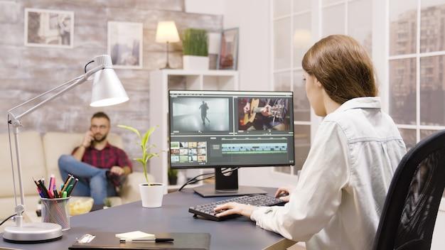 Zijaanzicht van video-editor die vanuit huis aan een project werkt. vriend op de achtergrond praat aan de telefoon.