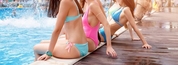 Zijaanzicht van vijf jonge dames, gekleed in kleurrijke zwemkleding.