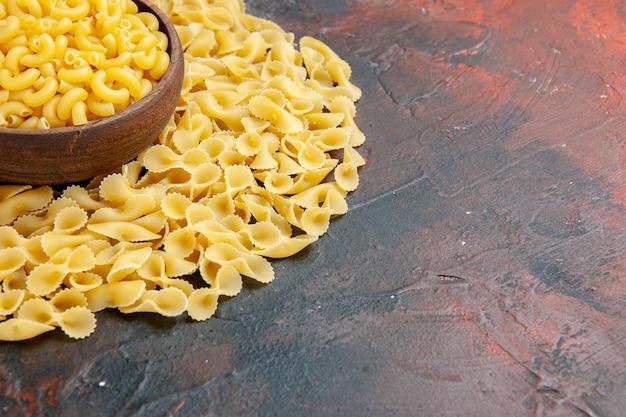 Zijaanzicht van vlinder ongekookte pasta's in een bruine kom aan de rechterkant van de gemengde kleurentafel
