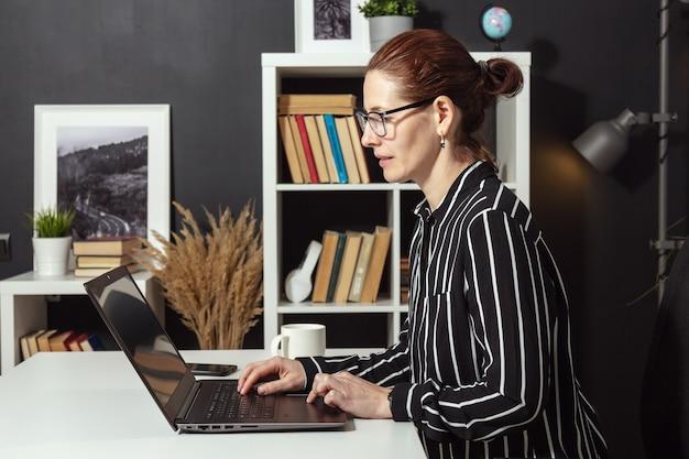 Zijaanzicht van volwassen geconcentreerde vrouw die op laptop werkt vanuit huis zittend aan een bureau, extern werk