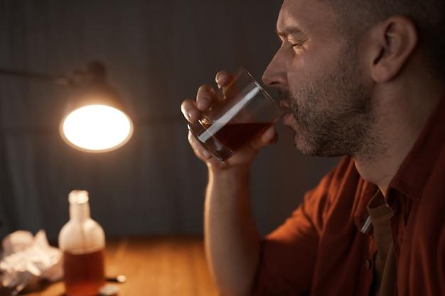 Zijaanzicht van volwassen man met glas en sterke alcohol drinken aan de tafel