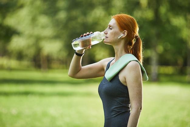 Zijaanzicht van volwassen roodharige fitness vrouw met handdoek op schouder drinkwater in park na het sporten