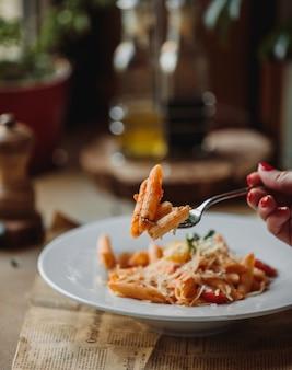 Zijaanzicht van vork met pasta met tomatensaus en parmezaanse kaas