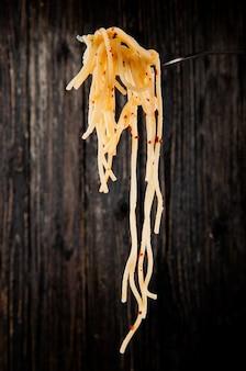Zijaanzicht van vork met spaghetti met chili vlokken rond op donker
