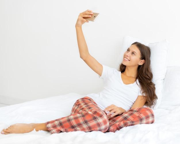 Zijaanzicht van vrij vrouwelijke selfie over de volledige lengte, blonde neemt foto op mobiele telefoon