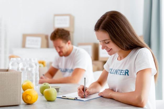 Zijaanzicht van vrijwilligers die aan voedseldonaties werken