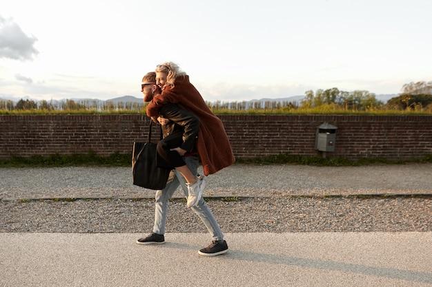 Zijaanzicht van vrolijk mooi meisje in stijlvolle kleding domineert haar vriendje, met rit op zijn rug. knappe jonge man met schattige vrouw. hipster paar plezier, buiten lachen
