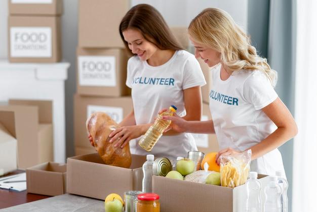 Zijaanzicht van vrolijke vrouwelijke vrijwilligers die voedselschenkingen voorbereiden