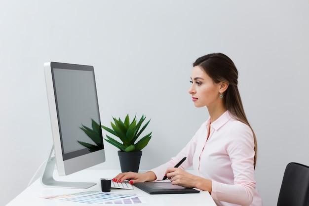Zijaanzicht van vrouw bij bureau dat met haar tablet werkt