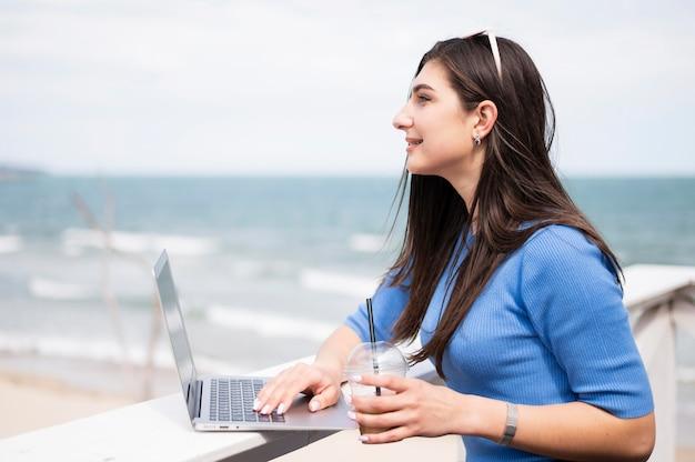 Zijaanzicht van vrouw bij het strand dat aan laptop werkt