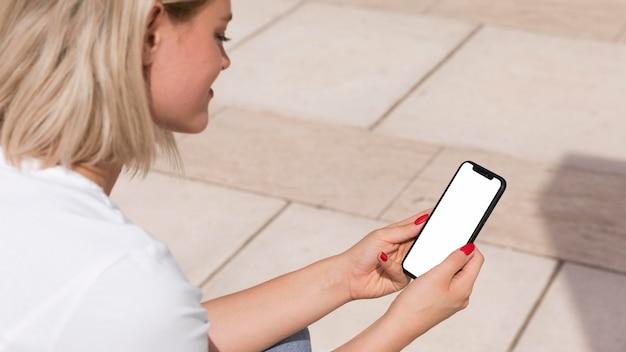 Zijaanzicht van vrouw buitenshuis met smartphone