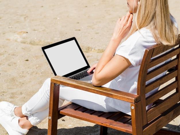 Zijaanzicht van vrouw die aan laptop in strandstoel werkt