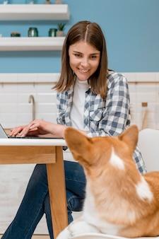 Zijaanzicht van vrouw die aan laptop met haar hond werkt