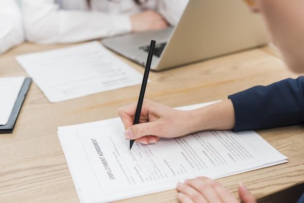 Zijaanzicht van vrouw die arbeidsovereenkomst ondertekenen