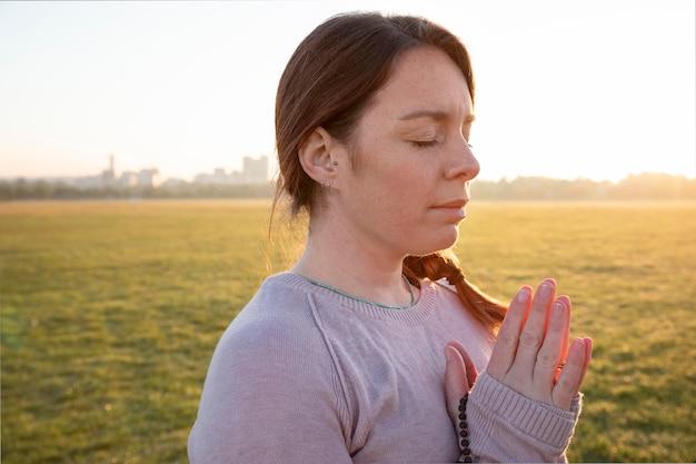 Zijaanzicht van vrouw die buitenshuis mediteert