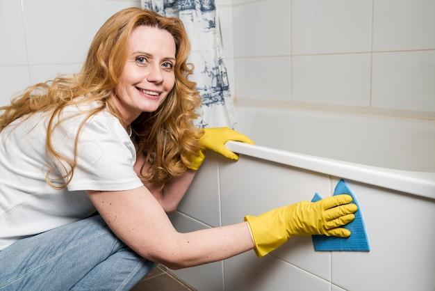 Zijaanzicht van vrouw die de badkuip schoonmaakt
