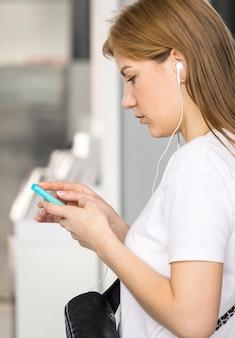 Zijaanzicht van vrouw die haar telefoon controleert
