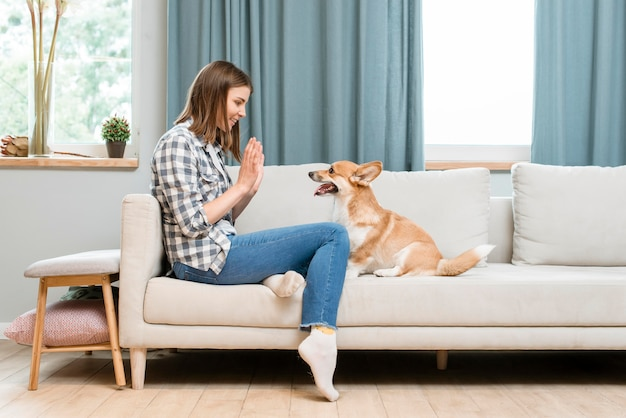 Zijaanzicht van vrouw die hond aan high-five vraagt
