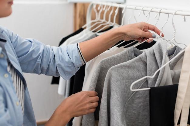 Zijaanzicht van vrouw die kleren op hangers schikt