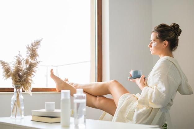 Zijaanzicht van vrouw die kuuroord van dag thuis genieten terwijl het hebben van koffie