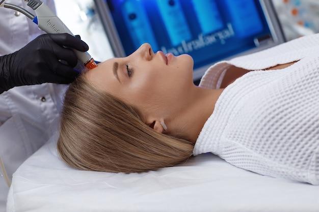 Zijaanzicht van vrouw die microdermabrasietherapie op voorhoofd ontvangt bij beauty spa. hydrafacial procedure in cosmetologie kliniek.