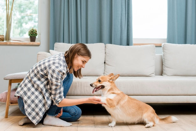 Zijaanzicht van vrouw die om de poot van haar hond vraagt