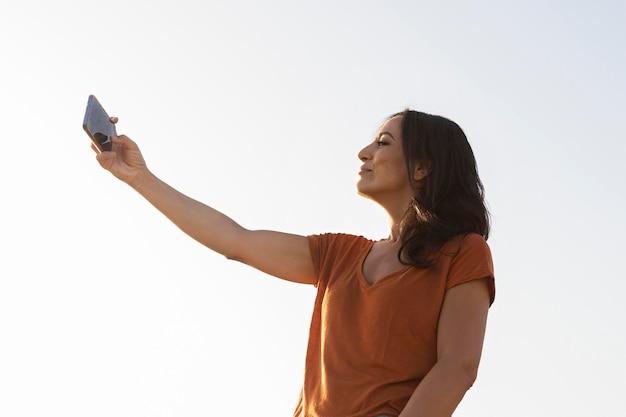 Zijaanzicht van vrouw die selfie in openlucht spreken