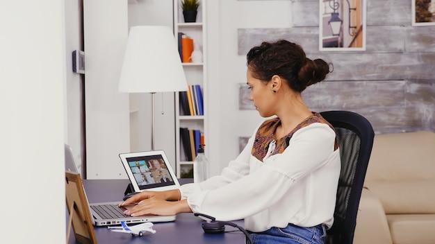 Zijaanzicht van vrouw die thuis op laptop werkt tijdens een videogesprek op tabletcomputer met collega's.