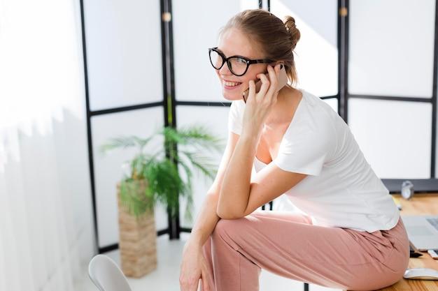 Zijaanzicht van vrouw die van huis terwijl aan de telefoon werkt