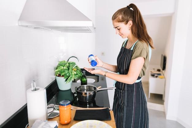 Zijaanzicht van vrouw die voedsel in de keuken voorbereidt