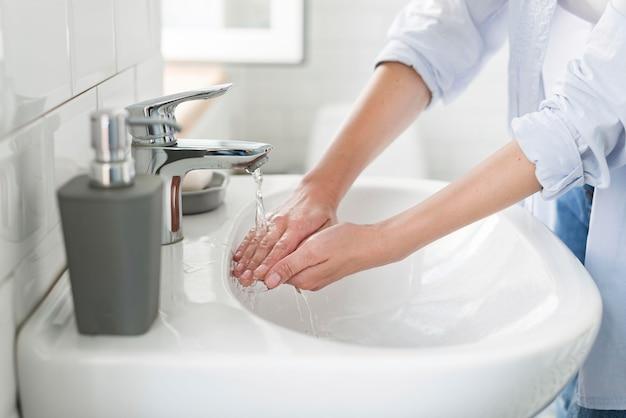 Zijaanzicht van vrouw die water gebruikt om haar handen te wassen