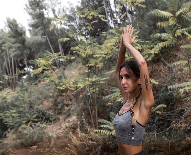 Zijaanzicht van vrouw doet yoga in de natuur met kopie ruimte