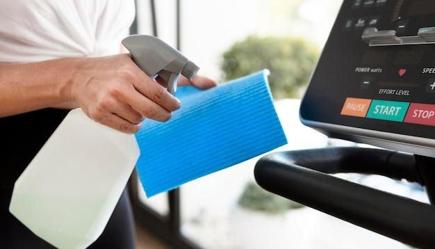 Zijaanzicht van vrouw fitnessapparatuur schoonmaken
