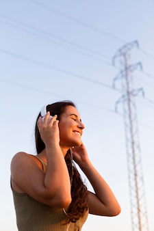 Zijaanzicht van vrouw genieten van muziek in de zon buiten